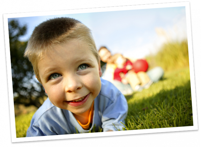 Closeup of young boy smiling and laying on grass with father and brother in distant background blurred out