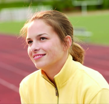Young woman smiling while standing on a track field