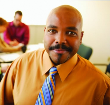 Smiling african american man in front of a conference table with fellow coworkers stilling in background blurred