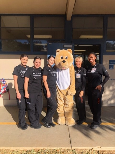 Bradley Jacoby, DO, pediatrician, Southern California Permanente Medical Group (bear costume), and Riverside Community College nursing students partner for the Teach Flu a Lesson program at Jackson Elementary School in Riverside, California.